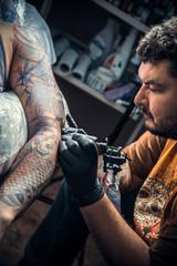Professional tattooist makes tattoo in studio