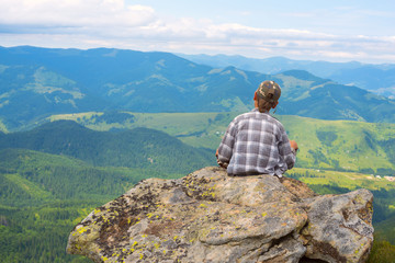 Dreaming boy sits on the cliff in front the mountains
