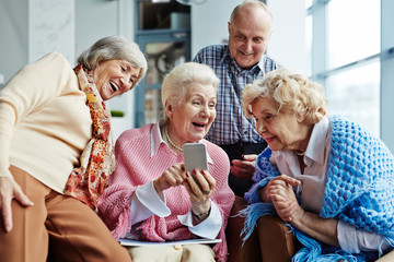 Four cheerful elderly people hanging out in spacious coffeehouse and looking through photos on modern smartphone