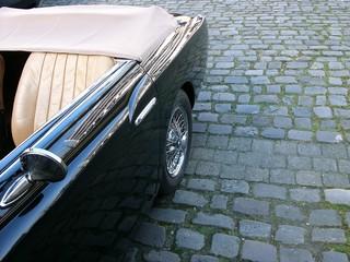 Beigefarbener Ledersitz eines glänzenden schwarzen Cabriolets der Fünfziger Jahre auf altem Kopfsteinpflaster am Hafen von Münster in Westfalen im Münsterland