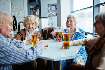 Three female and one male senior friends sitting in pub with glasses of beer and chatting animatedly with each other