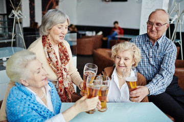Having good time with friends in pub: group of joyful senior people sitting at table and clanging glasses of beer together