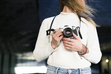 Young woman with camera, partial view