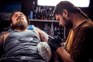 Tattooer makes cool tattoo in tattoo parlor