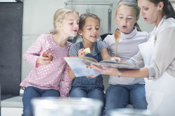 Mother and three girls in kitchen looking in book