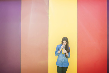 Smiling young woman in front of colourful striped wall drinking orange juice