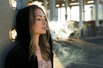 Portrait of young woman wearing hooded jacket smoking cigarette at backlight