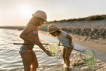 Spain, Menorca, two girls with dip nets on the beach