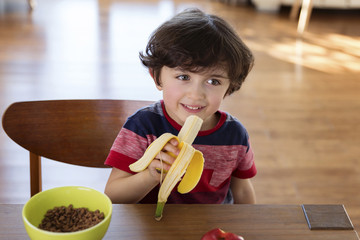 Portrait of smiling little boy sitting at the breakfast table eating banana