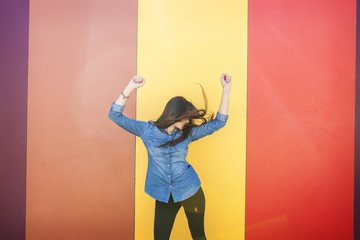 Happy young woman dancing in front of colourful wall