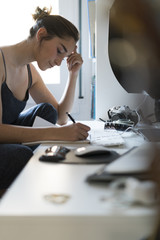 Young woman taking notes at desk