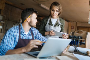 Pretty young carpenter and her bearded colleague brainstorming in workshop: he showing her something on computer screen while she looking at it with interest