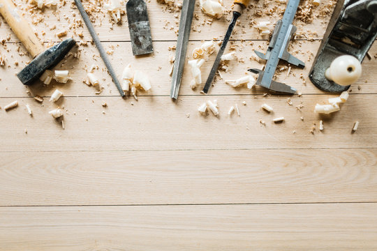 High angle view of shabby woodworking tools lying on wooden table, shavings scattered everywhere