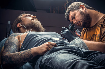 Professional tattooer posing in tattoo parlor