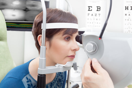 Woman with short haircut close-up from her side having eye examination at ophthalmology room in hospital, male oculist hand adjusting the device in foreground