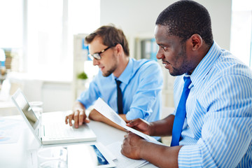 Confident Afro-American employee with document in hands looking at computer screen while his colleague working on modern laptop