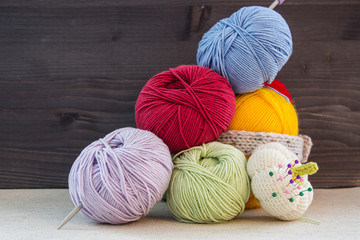 Multi-colored balls of yarn for knitting and pincushion on a dark wooden background. Selective focus.