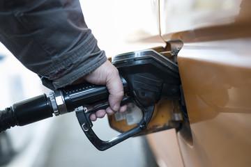 Männerhand hält Tankzapfen in Ronges Auto