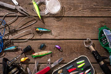 Fishing tackle - fishing spinning, fishing line, hooks and lures on wooden background.