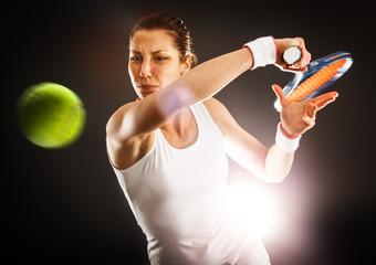 Tennis female player hitting ball with forehand.Studio shot.