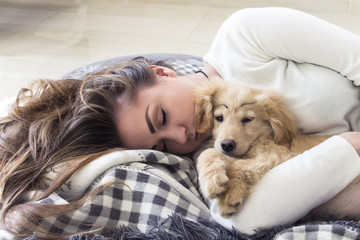 young pretty girl sleeps with puppy on the blanket