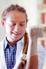 Young doctor with long dread locks posing for camera while putting on rubber gloves, clinic in background, medical concept