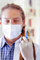 Young doctor with long dread locks posing for camera holding syringe, wearing facial mask covering mouth, clinic in background, medical concept