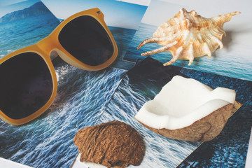 Yellow sunglasses, shell and pictures with the image of the sea on white surface