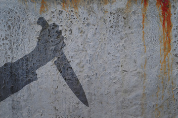 Human hand with killing knife silhouette in shadow on concrete wall and blood background, with space for text or image. Wall mural