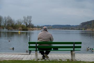 Mann sitzt alleine auf Parkbank