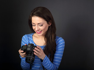 Happy toothy smiling young female photograph looking on the screen of camera and joying the photo on dark grey background