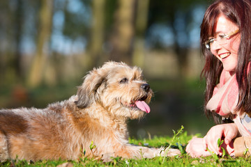 young woman and her dog lying on the grass
