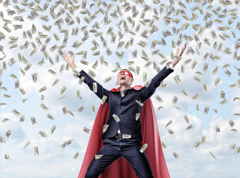 A smiling businessman in a superhero red cape with hands raised in success motion under money waterfall.