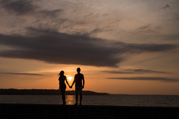 Silhouette of the couple in love in front of a sunset