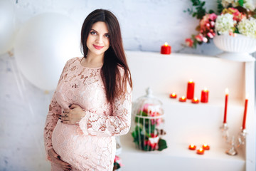 Young beautiful pregnant woman in pink dress on a light background