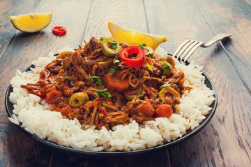 Slow Cooker Ropa Vieja, Cuban famously delicious shredded beef stew with pepper and olives on a black plate with a boiled rice and fresh lemon on the wooden table.