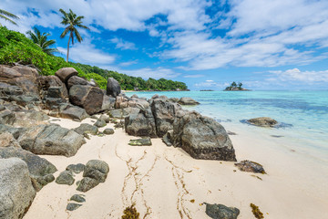 Tropical beach Anse Royale with granite boulders in the foreground at Mahe island, Seychelles - vacation background.