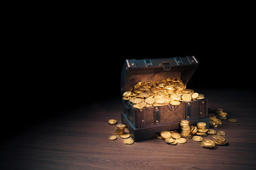 Open treasure chest with gold coins on a dark background