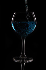 A glass with a blue liquid on a black background