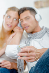 Couple sharing headphones, listening to cellphone