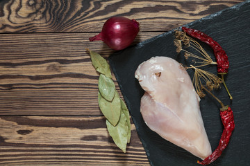 Raw uncooked chicken fillet on a cutting table with ingredients for cooking, on black stone board. Top view. Toned. Copy space.