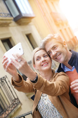 Couple taking selfie picture with smartphone in European city
