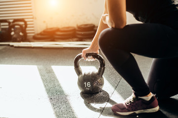 Young fitness woman lifting a heavy weight kettle bell at gym. Caucasian female athlete working out at gym. Fit young lady doing cross fit exercise.