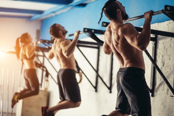 Group of tree attractive young male and female adults doing pull ups on bar in cross fit training...