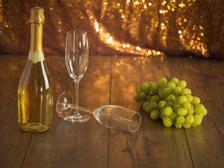 Bottle of champagne on a wooden table glasses and a cluster of grapes.