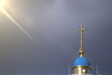 A large Christian cross on which falls a ray of sun through the clouds