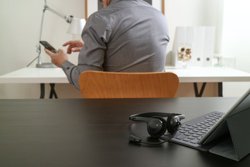 businessman using VOIP headset with digital tablet computer and smart phone,as concept communication and call center or customer service help desk in modern office