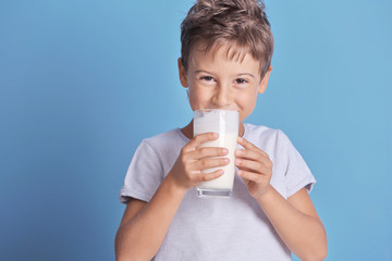 Cute kid drinking milk on blue background