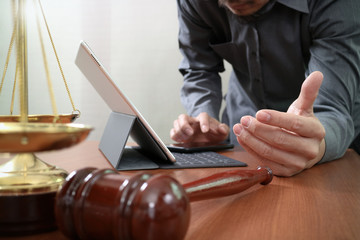 justice and law concept.Male lawyer in office with the gavel,working with smart phone and digital tablet computer and brass scale on wood table