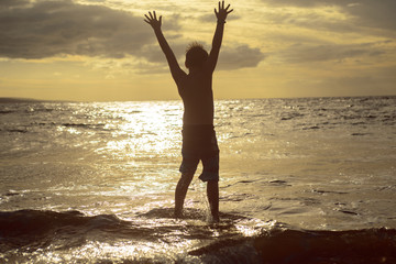 Silhouette of boy with open arms standing in the ocean